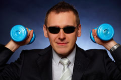 Confident businessman with dumbbells stock photography