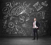 A confident businessman in formal suit is thinking about business development. A sketched brainstorm process is drawn on the huge. Black chalkboard Stock Images