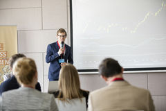 Confident businessman giving presentation in seminar hall at convention center.  stock photography