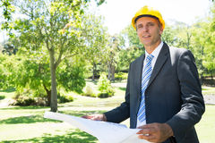 Confident businessman holding blueprint Stock Photography