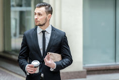 Confident businessman holding a business newspaper and looking a Stock Image