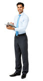 Confident Businessman Holding Clipboard Stock Photo