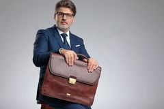 Confident businessman holding his briefcase while sitting. On a stool, wearing a blue suit and glasses on gray studio background stock photo