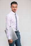 Confident businessman holding laptop computer. Portrait of a confident businessman holding laptop computer and looking at camera over gray background Royalty Free Stock Photos
