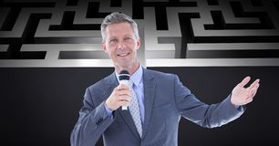 Confident businessman holding microphone against maze stock images
