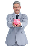 Confident businessman holding piggy bank in both hands Stock Photo