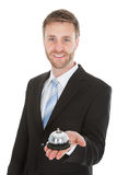 Confident Businessman Holding Service Bell. Portrait of confident businessman holding service bell over white background Stock Image