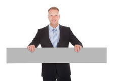 Confident Businessman Holding Wooden Plank Royalty Free Stock Images