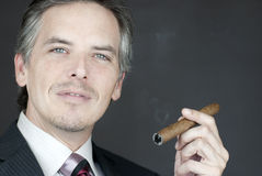 Confident Businessman Holds Cigar Stock Image