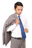 Confident businessman with jacket draped over shoulder, Stock Image
