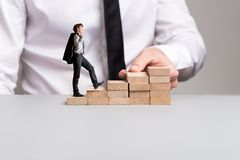 Confident businessman with jacket over his shoulder walking up the stairs stock images