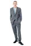 Confident businessman keeping his hands in pockets Royalty Free Stock Photo