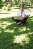 Confident businessman with laptop. Full length portrait of confident businessman with laptop sitting on grass in park Stock Photo