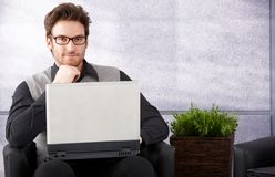 Confident businessman with laptop smiling Royalty Free Stock Image