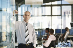 Confident Businessman Leaning On Glass Door Stock Images