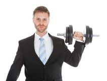 Confident businessman lifting dumbbell Royalty Free Stock Image
