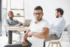 confident businessman looking at camera while colleagues working at table stock photography