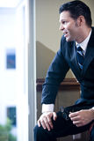 Confident businessman looking out office window Stock Photography