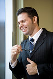 Confident businessman looking out office window Stock Photo