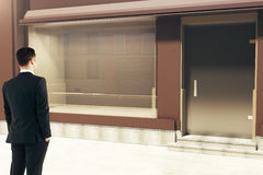 Confident businessman looking at storefront. Confident businessman looking at empty clean storefront in daylight. Side view, Mock up, 3D Rendering Stock Photos
