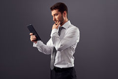 Confident businessman looking at tablet pc Stock Photography