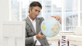 Confident businessman looking at a terrestrial globe Stock Photo