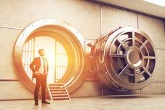 Confident businessman near open vault door, toned. Confident businessman is standing near wide open vault door. Concept of money saving. 3d rendering. Toned royalty free stock photography