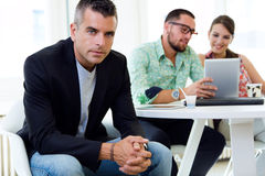 Confident businessman in office with his team. Stock Photo