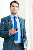 Confident businessman outdoor using phone Stock Photo