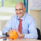 Confident Businessman With Piggybank At Desk Royalty Free Stock Photo