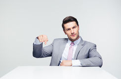 Confident businessman pointing finger down Stock Photos