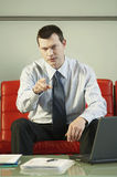 Confident Businessman Pointing While Sitting On Red Couch Royalty Free Stock Photo