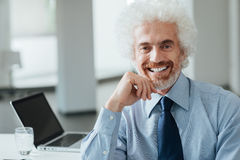 Confident businessman posing with hand on chin Royalty Free Stock Image