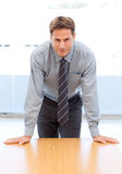 Confident businessman posing leaning on a table Royalty Free Stock Image