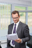 Confident businessman reading a document Royalty Free Stock Images