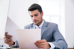 Confident businessman reading documents in office Stock Photo