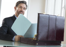 Confident Businessman Reading Notes In File At Desk Stock Photo