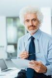 Confident businessman reading paperwork Stock Photography