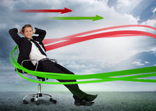 Confident businessman reclining in swivel chair with red and gre Stock Photography