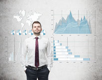 Confident businessman in red tie and blue and white graphs on co Royalty Free Stock Image