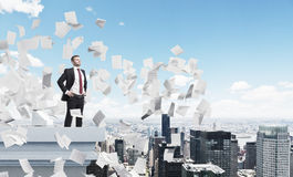 Confident businessman on a roof, papers Stock Image