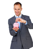 Confident businessman saving money in a piggy-bank Royalty Free Stock Image