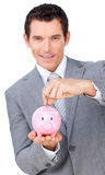 Confident businessman saving money in a piggybank. Against a white background Royalty Free Stock Image