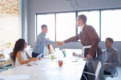 Handsome business men shaking hands. Conference on the office background. Handshake concept. Confident businessman shaking hands with a handsome men on the Stock Photos