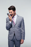 Confident businessman shouting on the phone. Over gray background Stock Image