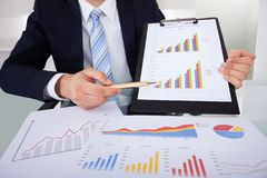 Confident businessman showing graphs in office Stock Images