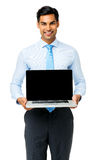 Confident Businessman Showing Laptop. Portrait of confident businessman showing laptop against white background. Vertical shot royalty free stock image