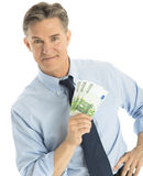 Confident Businessman Showing One Hundred Euro Banknotes. Portrait of confident mature businessman showing one hundred euro banknotes against white background Stock Photography