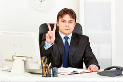 Confident businessman showing victory gesture Royalty Free Stock Photography
