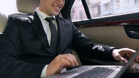 Confident businessman sitting in car with laptop, pleasantly surprised good news. Stock footage stock video footage